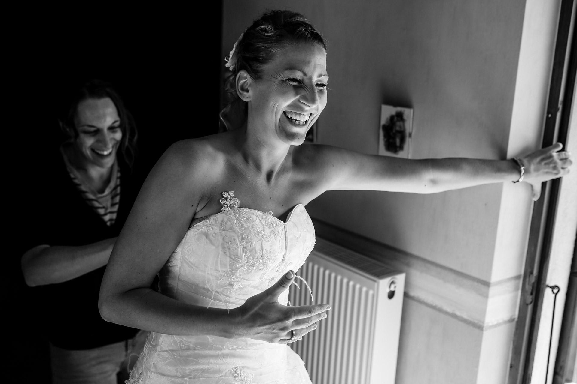 la mariee qui eclate de rires en s'habillant