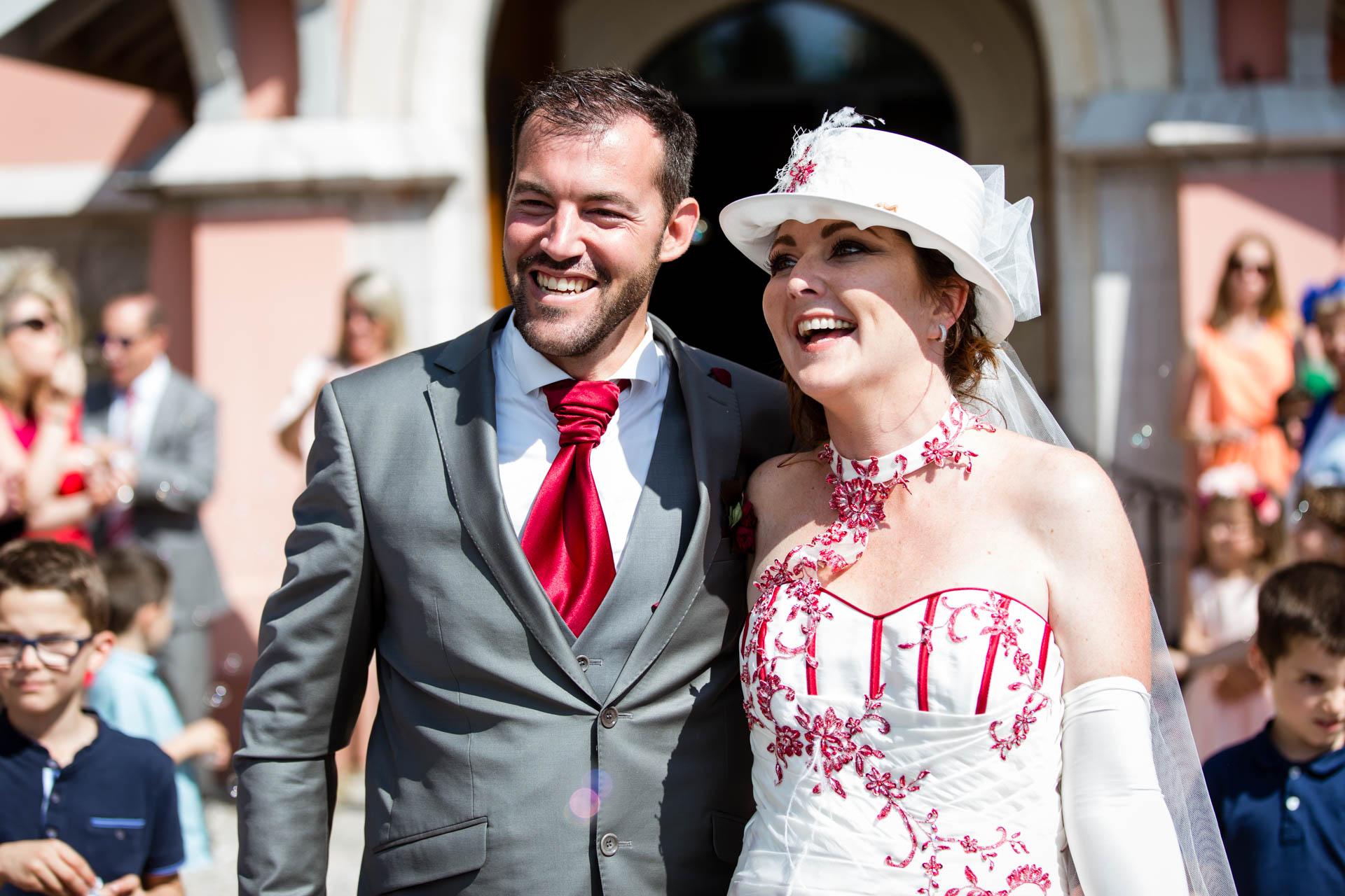 Mariage Coppet eglise Saint Robert sortie des maries en souriant