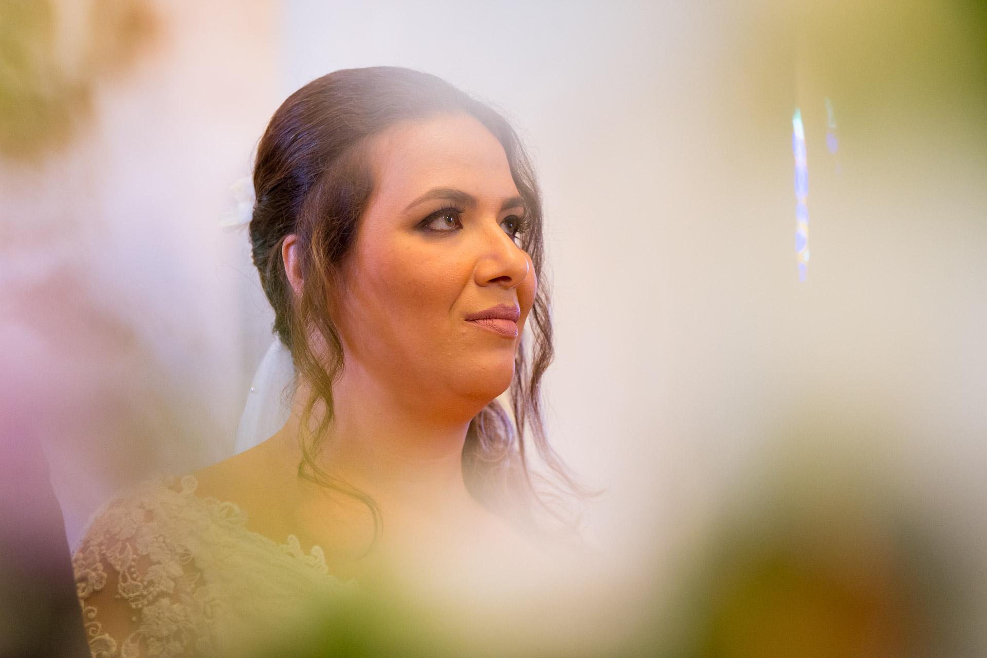 portrait de la mariee dans l'eglise avec les fleurs en premier plan