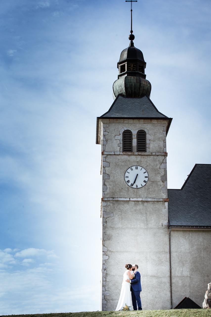 Mariage Mont Saxonnex photo de couple devant l'eglise avec ciel bleu
